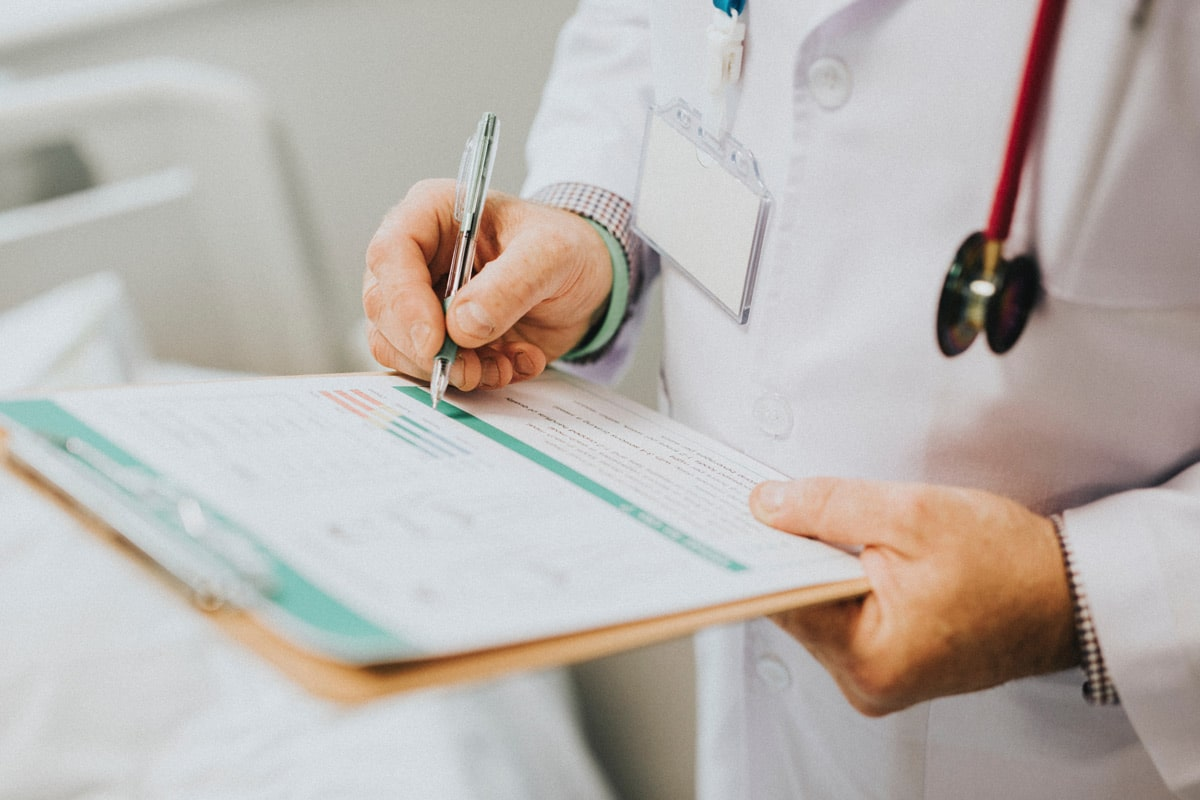 Doctor holding clipboard with patient chart.